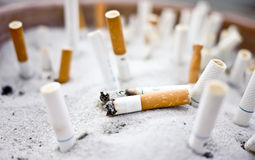 Cigarette butts in ashtray. Many cigarette butts in the ashtray. photo taken in the natural light Stock Photos
