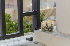 Cigarette butts in ashtray on a balcony. Smoking inside not allowed Stock Photo