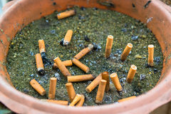 Cigarette butts in container outdoor ashtray Stock Images