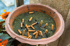 Cigarette butts in container outdoor ashtray Royalty Free Stock Photography