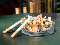 Cigarette butts in a glass ashtray. Stock Photo