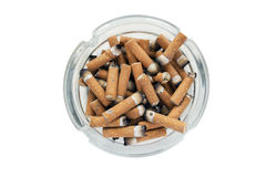 Cigarette butts. Glass ashtray full of cigarette butts on white background Stock Images