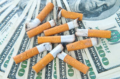Cigarette butts llaying on money Stock Photography
