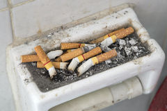 Cigarette butts. Many cigarette butts close up in ash receiver Royalty Free Stock Photos