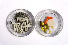 Cigarette butts and pills. The best for: addictions, smoking, addiction to medication, health issues Stock Image