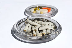 Cigarette butts and pills Stock Photography