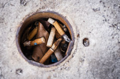 Cigarette butts in pole hole. Pile of cigarette butts in pole hole Stock Photo