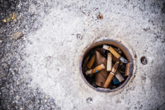 Cigarette butts in pole hole. Pile of cigarette butts in pole hole Stock Image