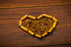 Cigarette butts shaped into a heart lying on wooden surface, tobacco spread around middle, seen from above Stock Image