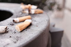 Cigarette butts. Cigarette stubs on the side of a trash can - selective focus on one stub, copy space to the right Stock Images