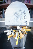 Cigarette butts, stuffed into an on street receptacle Stock Photos