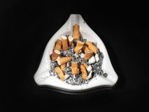Cigarette butts. White ceramic ash tray full of cigarette butts on black background Royalty Free Stock Photo