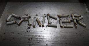 Cigarette can cause disease and dead on metal background Stock Images