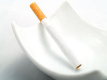 A cigarette in a clean white ashtray Royalty Free Stock Photo
