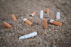 Cigarette. Close up cigarette burning in sand closeup Royalty Free Stock Photos