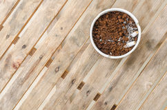 Cigarette and coffee ground in a ceramic ashtray and on wood tab Royalty Free Stock Photo