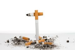 Cigarette crux. A crux is build with cigarettes where other used cigarettes are lying on the floor Royalty Free Stock Photo