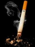 Cigarette danger. Cigarette with skull on black background Royalty Free Stock Image
