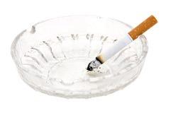 Cigarette dans le cendrier en verre Photographie stock libre de droits