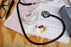 Cigarette dans le cendrier et le stéthoscope, moniteur de tension artérielle, pilules Photos stock