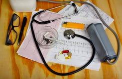 Cigarette dans le cendrier et le stéthoscope, moniteur de tension artérielle, pilules Photographie stock