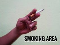 Cigarette de prise de main Photographie stock libre de droits