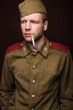 Cigarette de tabagisme et regards de soldat russe de la deuxième guerre mondiale à quelque chose Image libre de droits