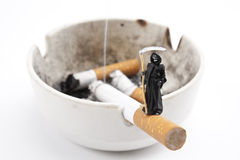 Cigarette and Death. Miniature Death standing on Cigarette Stock Photography