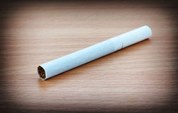 Cigarette on desk Royalty Free Stock Images