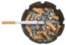 Cigarette in Dirty Ashtray. Lit cigarette in a full ashtray Stock Photos