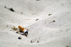 Cigarette. End thrown on the beach stock photo