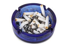 Cigarette ends in blue ashtray isolated Royalty Free Stock Image