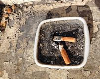 Cigarette ends or butts in an ash tray. Royalty Free Stock Images