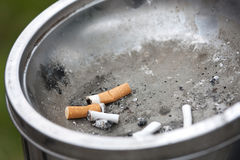 Cigarette Ends in a Public Ashtray. Cigarette Ends lying in a Public Ashtray in a City Park Stock Images