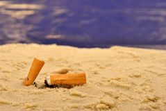 cigarette ends on a sandy beach Royalty Free Stock Image