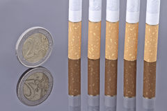 Cigarette and the 2 Euro coin Stock Image