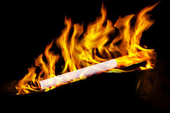 Cigarette in fire. Cigarette burning in fire. Illustration. Isolated on black. Stop smoking collection Stock Photography