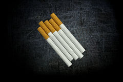 Cigarette. Five cigarettes lying on a gray background Royalty Free Stock Photos