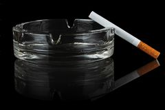 Cigarette and glass ashtray. Stock Image
