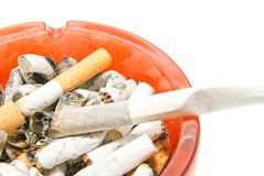 Cigarette in glass ashtray with butts Stock Photos