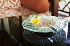 Cigarette and glass hotel ashtray on table with frangipani flower. Stock Photography