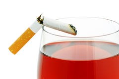 Cigarette with a glass of wine. Broken cigarette on a glass of wine stock photo