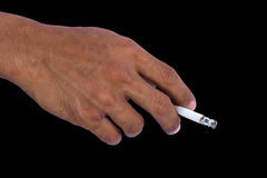 Cigarette in hand. Cigarette in hand with a black background Stock Image