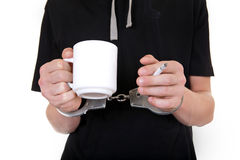Cigarette in a Hand with Handcuffs Stock Photos