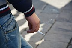Cigarette in a hand Stock Images