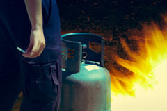 Cigarette in hand near gas tank cylinder can ignition of flammab Royalty Free Stock Image