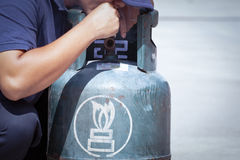 Cigarette in hand near gas tank cylinder can ignition of flammab Stock Photo