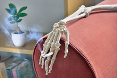 Cigarette in hand of skeleton. On arm of sofa royalty free stock photo