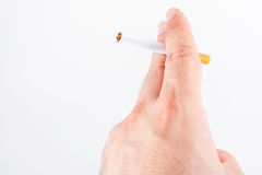 Cigarette in a hand on the white Stock Images