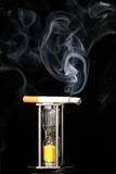 Cigarette and hour glass. Burning cigarette on hour glass which has run out, isolated on black background stock image
